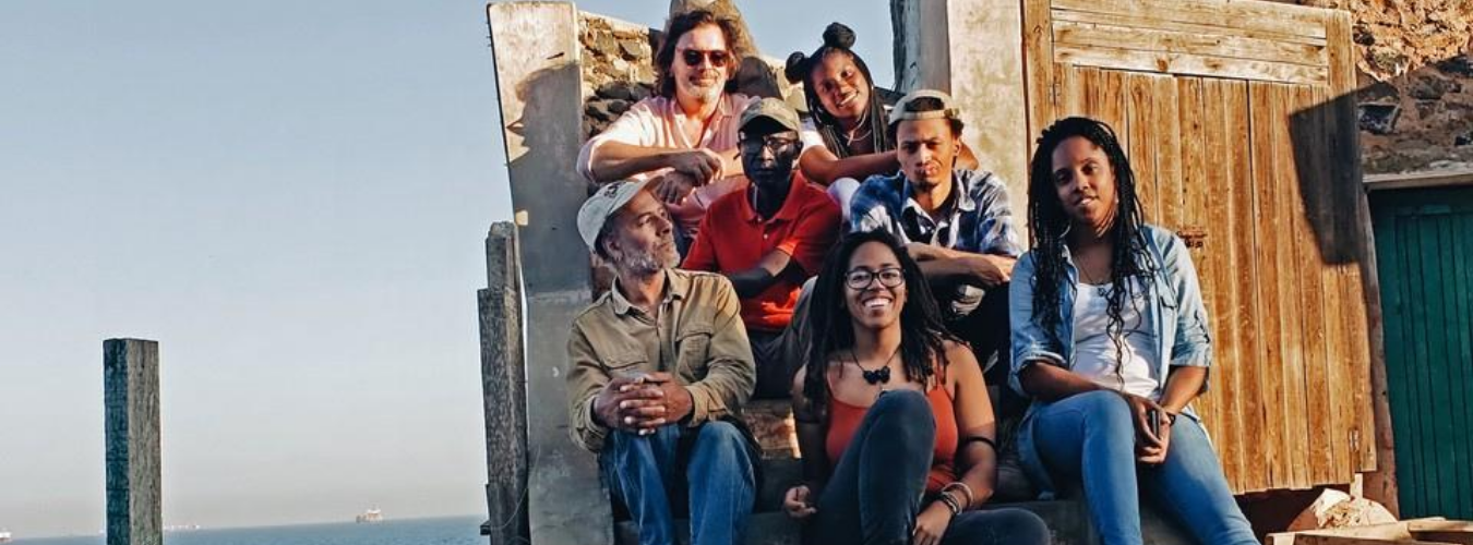 five art students with two professors sitting with an ocean behind them in Senegal
