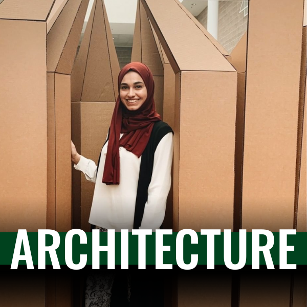 female student wearing a white shirt and a hijab standing inside a hand made cardboard structure