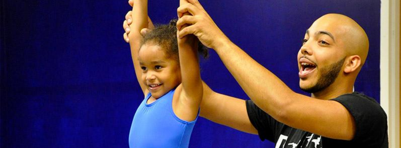 Black male alumnus opened his own dance studio in Charlotte, pictured with young dance student helping with position