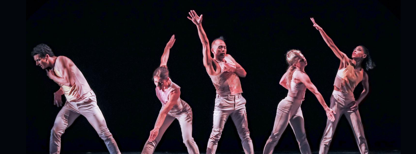 Five adult dancers in a line with a black background reaching different directions