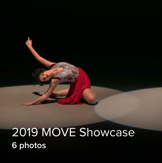 solo shot of a dancer in a red skirt sitting on the floor, reaching up in a spotlight