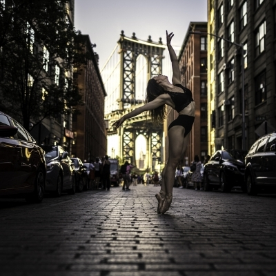Laura Dearman in a red leotard jumping in NYC Grand Central Station