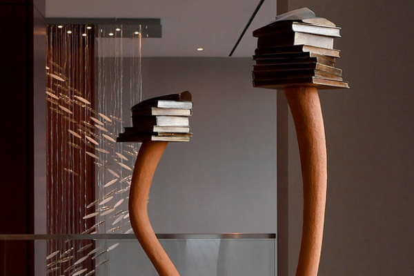 Two copper poles holding a stack of books