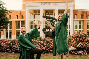 Music education graduates throwing their grad cap in front of Robinson Hall