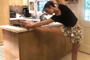 student stretching in kitchen