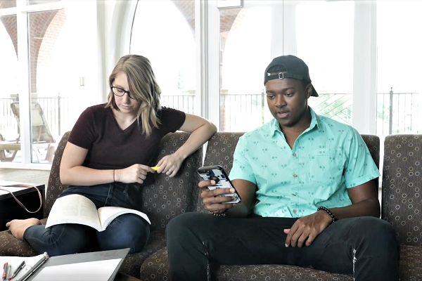 screen shot from video - two students on couch